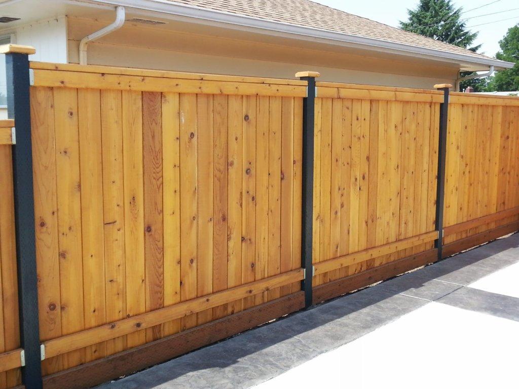 Деревянный забор с железными столбами