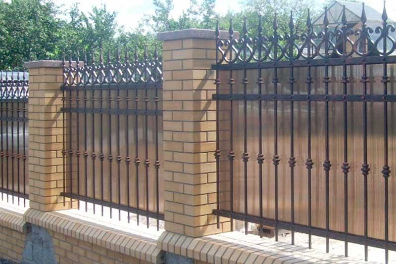 Кованый забор с поликарбонатом и кирпичными столбами